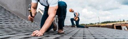 Photo for Panoramic shot of handyman holding hammer while repairing roof near coworker - Royalty Free Image