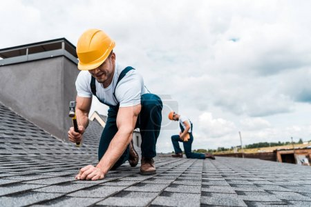 selective focus of handyman holding hammer while repairing roof near coworker