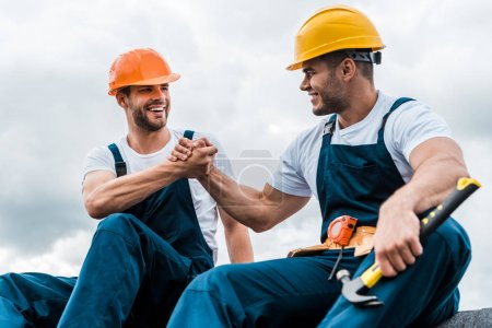 Photo for Happy handymen holding hands while smiling against sky - Royalty Free Image
