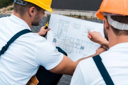 selective focus of builders in helmets looking at blueprint