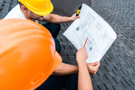 Photo for Selective focus of architect in helmet holding pencil near blueprint and coworker - Royalty Free Image