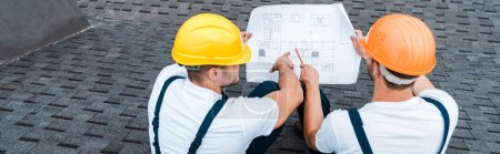 Photo for Panoramic shot of builders in helmets looking at blueprint - Royalty Free Image