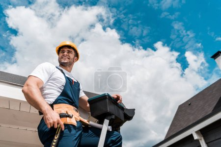 Photo for Low angle view of happy repairman in helmet holding hammer and toolbox - Royalty Free Image