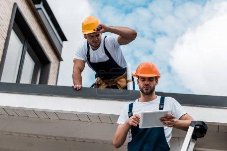 Photo pour Vue d'angle bas de l'homme regardant le collègue dans le casque utilisant la tablette numérique - image libre de droit