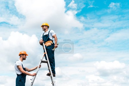 Photo for Cheerful repairmen standing on ladder and smiling against blue sky with clouds - Royalty Free Image