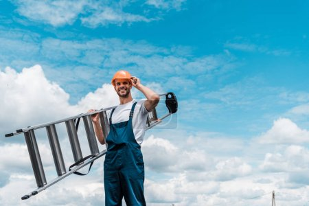 Photo for Cheerful repairman holding ladder and smiling against blue sky with clouds - Royalty Free Image