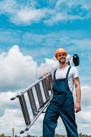 Photo pour Échelle heureuse de fixation de réparateur et souriant contre le ciel bleu avec des nuages - image libre de droit
