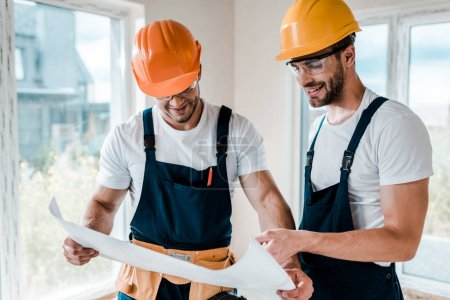 Photo for Happy architects in goggles and helmets looking at blueprint - Royalty Free Image