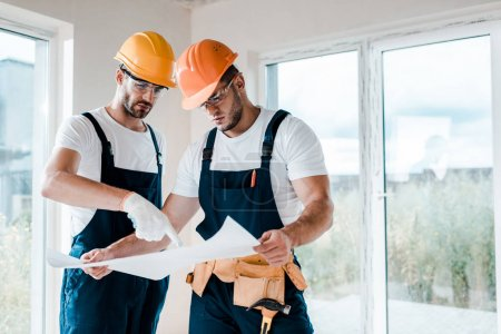 Photo for Handsome builders in goggles and helmets looking at blueprint - Royalty Free Image