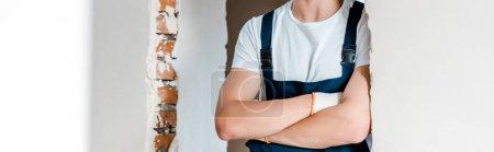 Foto de Disparo panorámico de reparador de pie con los brazos cruzados en la casa - Imagen libre de derechos