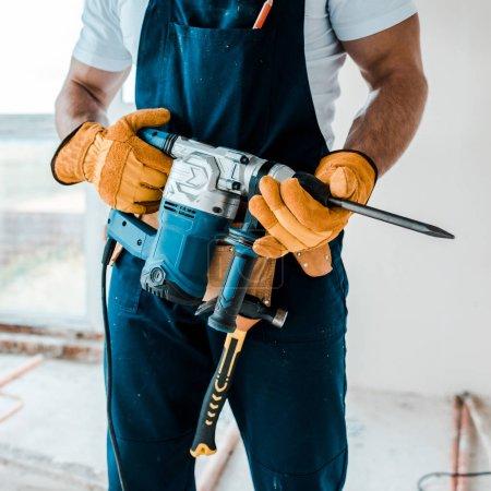 Foto de Vista recortada del obrero en guantes uniformes y amarillos que sostienen el taladro martillo - Imagen libre de derechos