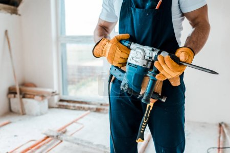Photo for Cropped view of workman in yellow gloves holding hammer drill - Royalty Free Image