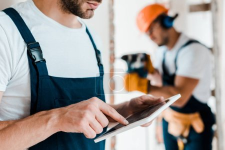 Photo for Cropped view of bearded workman pointing with finger at digital tablet - Royalty Free Image