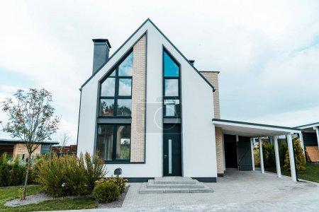 nouvelle maison de luxe près des arbres verts et des buissons sur l'herbe