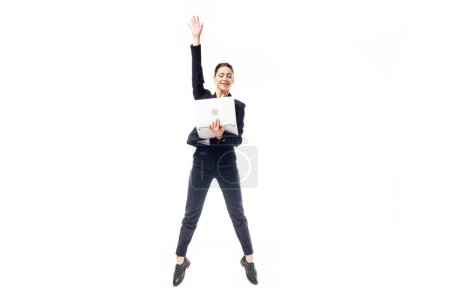 Photo for Attractive businesswoman jumping while holding laptop isolated on white - Royalty Free Image