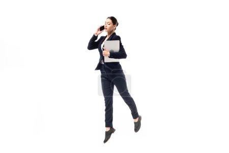 Foto de Joven mujer de negocios hablando en smartphone y sosteniendo portátil mientras baila aislado en blanco - Imagen libre de derechos