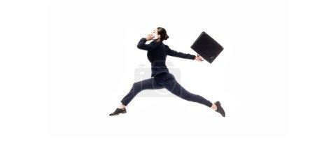 panoramische Aufnahme einer jungen Geschäftsfrau mit Aktentasche, die schwebt, während sie auf einem Smartphone spricht, isoliert auf Weiß