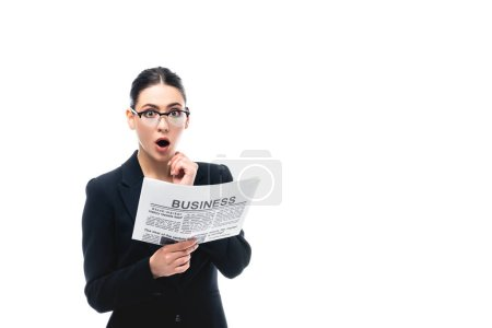shocked businesswoman looking at camera while holding business newspaper isolated on white