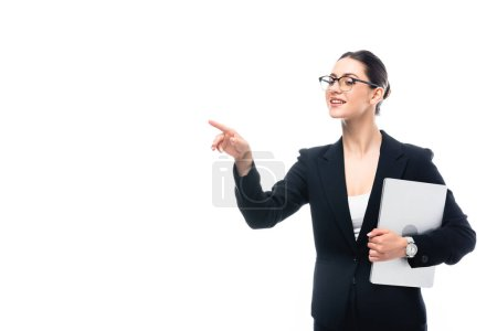 beautiful businesswoman pointing with finger while holding laptop isolated on white