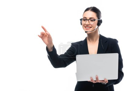 Foto de Operador del centro de llamadas alegre en auriculares apuntando con el dedo mientras sostiene el ordenador portátil aislado en blanco - Imagen libre de derechos