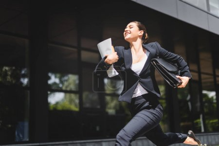 Photo for Happy businesswoman running and smiling while holding briefcase and folder - Royalty Free Image