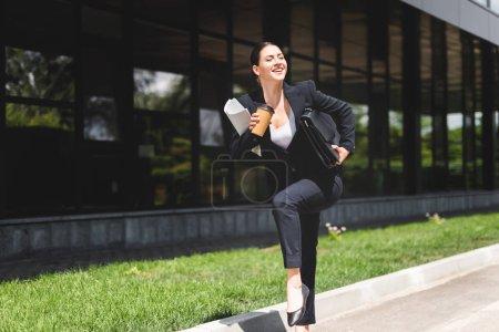 Photo pour Femme d'affaires heureuse tenant la mallette et le café pour aller tout en courant dans la rue - image libre de droit