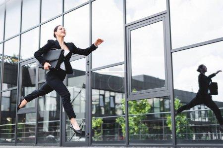 Photo pour Femme d'affaires heureuse lévitation sur la rue tout en retenant la mallette - image libre de droit
