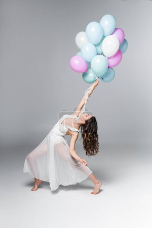 Photo for Graceful ballerina in white dress dancing with festive balloons on grey background - Royalty Free Image