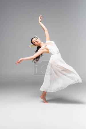 Photo pour Gracieuse, jolie ballerine en robe blanche dansant sur fond gris - image libre de droit
