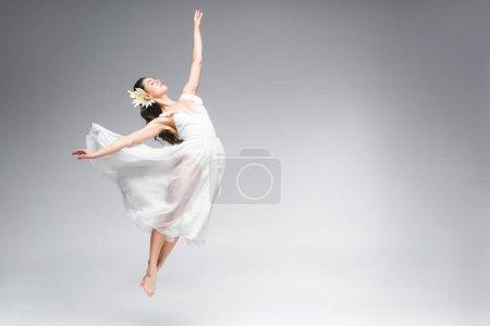 Photo pour Gracieuse ballerine en robe blanche sautant tout en dansant sur fond gris - image libre de droit