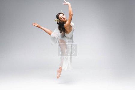 Photo pour Jeune belle ballerine en robe blanche sautant sur fond gris - image libre de droit