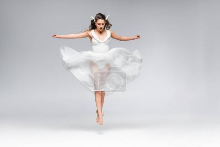 young attractive ballerina in white dress jumping while dancing on grey background