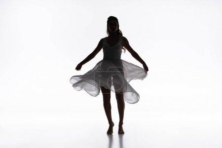 Photo pour Jeune ballerine gracieuse en robe blanche dansant sur fond gris - image libre de droit