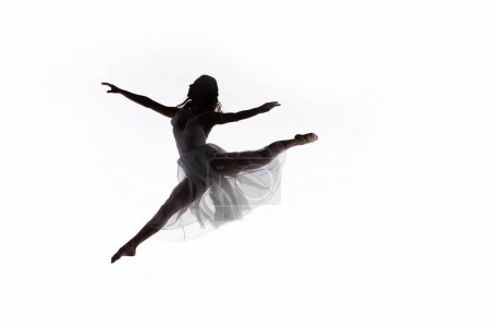 Young graceful ballerina jumping while dancing iso...