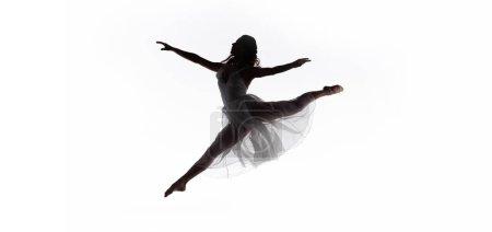 Photo pour Plan panoramique de la jeune ballerine gracieuse sautant tout en dansant isolé sur blanc - image libre de droit