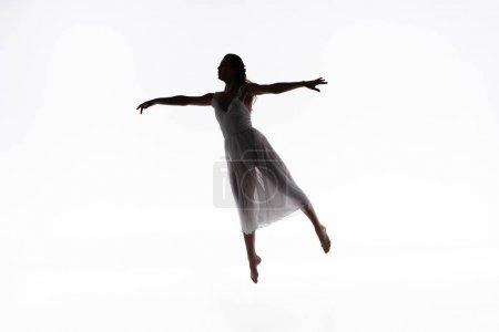 Photo pour Jeune, gracieuse ballerine sautant tout en dansant sur fond blanc - image libre de droit