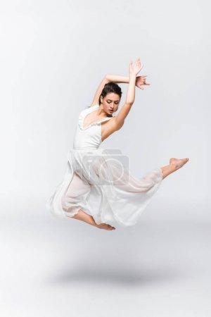 Photo pour Belle jeune ballerine dansant en robe blanche sur fond gris - image libre de droit