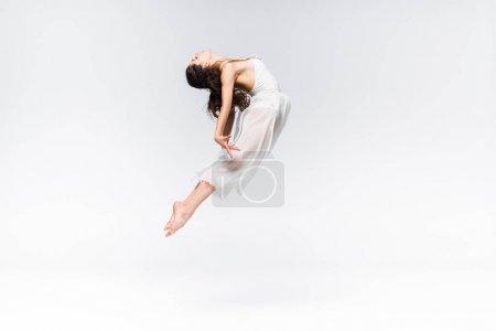 Photo pour Vue latérale de la gracieuse jeune ballerine sautant en danse sur fond gris - image libre de droit