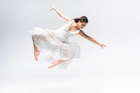 Photo pour Belle ballerine en robe blanche sautant en danse sur fond gris - image libre de droit