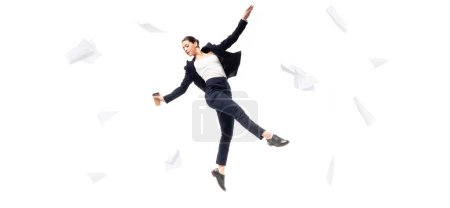 panoramic shot of businesswoman holding paper cup while levitating surrounded with flying papers isolated on white