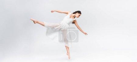 panoramic shot of graceful ballerina dancing on grey background