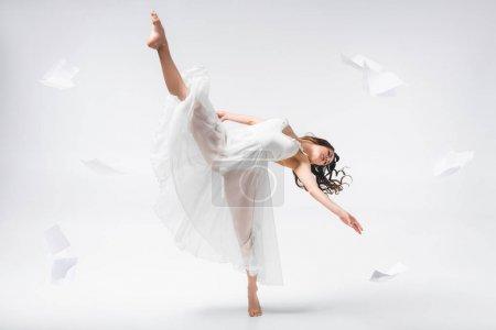 Photo pour Belle ballerine dansant entourée de papiers volants sur fond gris - image libre de droit