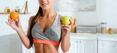Photo pour Plan panoramique de jeune femme heureuse en tenue de sport tenant des fruits savoureux - image libre de droit