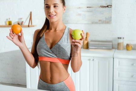 Photo pour Jeune femme heureux dans des vêtements de sport retenant des fruits savoureux - image libre de droit