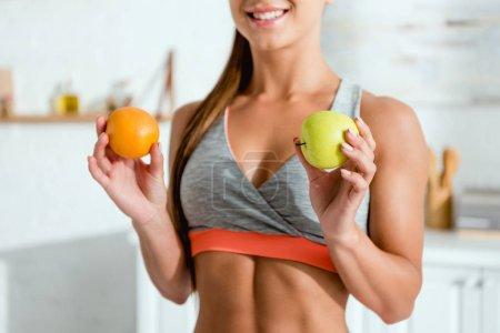 Photo pour Vue recadrée de jeune femme heureuse dans des vêtements de sport retenant des fruits savoureux - image libre de droit