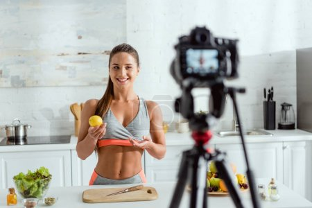 Photo for Selective focus of happy girl holding lemon and looking at digital camera - Royalty Free Image