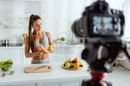 Photo for Selective focus of attractive and athletic girl holding apple and banana near digital camera - Royalty Free Image