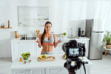 Selektiver Fokus attraktiver Videoblogger, die in der Nähe von Früchten und Digitalkameras gestikulieren