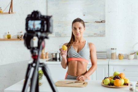 Photo pour Foyer sélectif de fille tenant pomme et regardant appareil photo numérique - image libre de droit