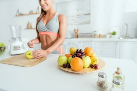 selective focus of tasty fruits on plate near cheerful girl